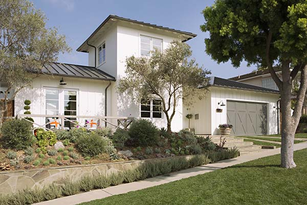 The Exterior Of Home Is Painted White With A Charcoal Roof And Gray Garage Door That Adds Contrast To It