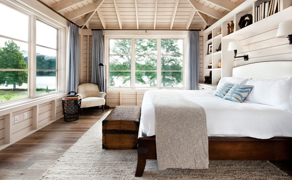 In this by foot master bedroom, Ashley Whittaker upped the cozy factor by covering the walls with a large-scale, blue-and-green flowering tree motif. The densely patterned wallpaper makes the large room feel more snug, and the crisp white headboard, lamps, and bedding give the eye a place to rest.