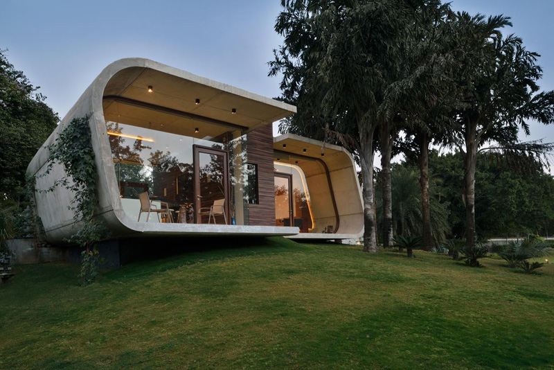 A curved concrete contemporary pool house in india home Small house indian style